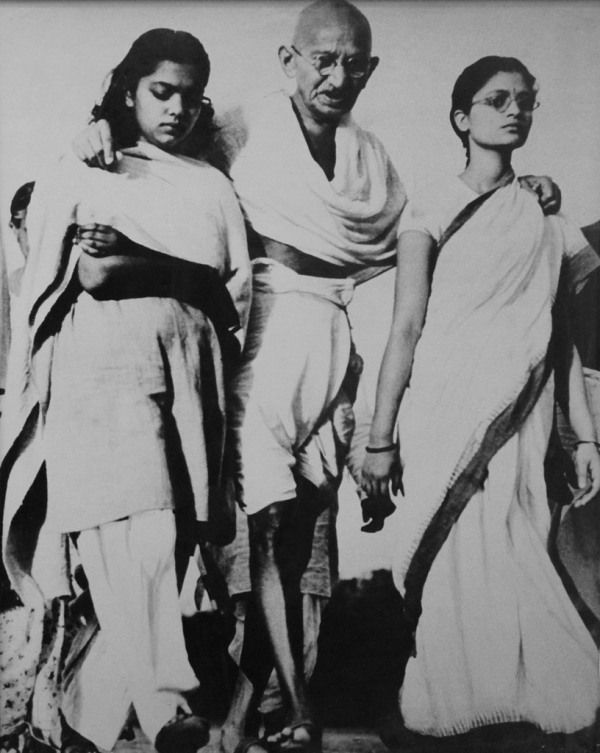 Mahatma Gandhi Leaning On Two Women