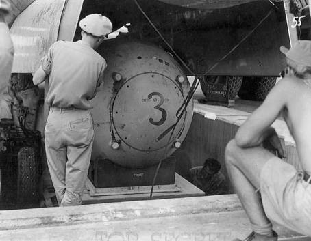 Fat Man test unit being raised from the pit into the bomb bay of a B-29