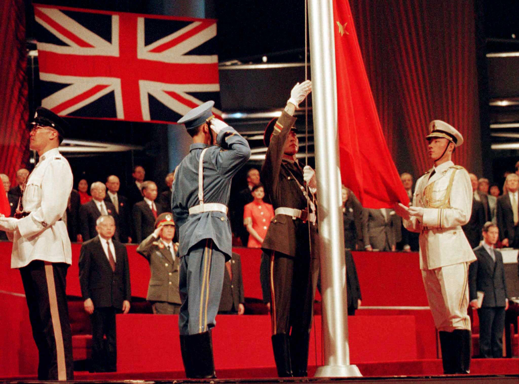 The Chinese flag is raised by People's Liberation Army soldiers at the handover ceremony in Hong Kong in this July 1, 1997 file photograph. Hong Kong returned to Chinese sovereignty at midnight after 156 years of British colonial rule 17 years ago today. REUTERS/Files (CHINA - Tags: ANNIVERSARY POLITICS)