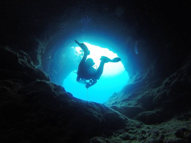 A diver in underwater sea cave